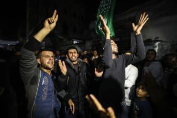 パレスチナ自治区ガザの難民キャンプで、イスラエルに抗議する人々=13日(ゲッティ=共同)