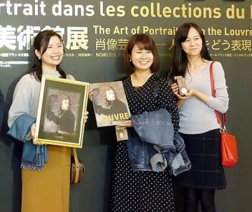 来場者10万人目になり、友人とともに記念品を受け取った細谷さん(左端)=13日、大阪市天王寺区の市立美術館