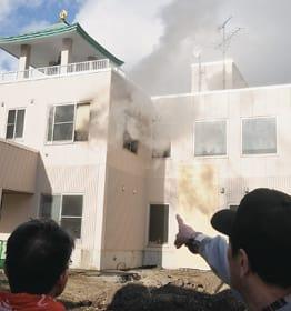 煙が立ち上る紋鼈寺に隣接する会館=13日午後1時6分、伊達市末永町