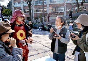 甲冑(かっちゅう)姿の大洲市職員から説明を聞きながらいもたきを味わう来場者