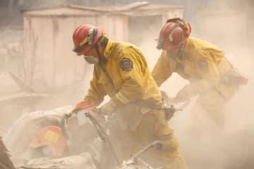 米カリフォルニア州の山火事で、燃えた家を調べる消防士=13日(ロイター=共同)