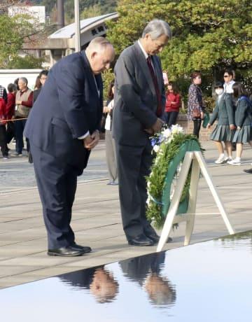 賢人会議のメンバーを代表し、平和祈念像前に献花するリントン・ブルックス氏(左)と白石隆氏=14日午前、長崎市の平和公園