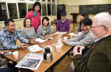 毎週金曜夜に開かれている会話サークル。セイルズさん(右端)や参加者が英語や日本語でコミュニケーションを楽しんでいる=9日午後8時すぎ