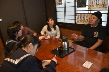 地域の魅力を探る取材活動で、居酒屋を営む坂口弦太さん(右)の話を聞く若者たち=鉾田市串挽