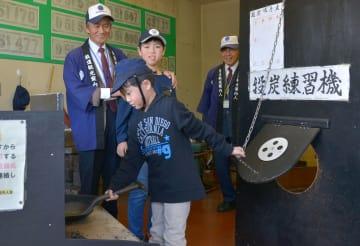 SL館にある投炭練習機で、SLの運転技術を子どもたちに教える人吉鉄道観光案内人会の立山勝徳会長(左)ら=人吉市