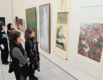 大分武漢友好美術展で作品を眺める来場者たち=14日午前、大分市の県立美術館