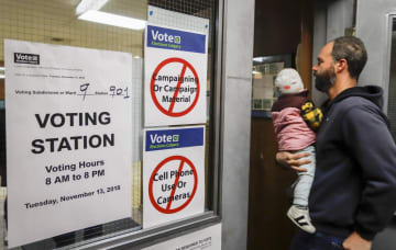 冬季五輪招致の賛否を問う住民投票に向かう男性=13日、カルガリー(AP=共同)
