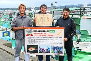 【賞状を手に受賞を喜ぶ岩谷水産の岩谷昇さん(中央)ら=13日、和歌山県串本町大島で】