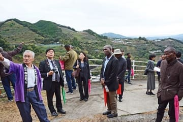 【石神忠夫会長(左)から話を聞くエチオピアとウガンダの農業担当職員ら=13日、和歌山県田辺市上芳養で】