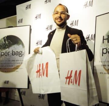 ルーカス・セイファート社長。右手にプラスチック製ショッピングバッグ、左手に紙製バッグを掲げている