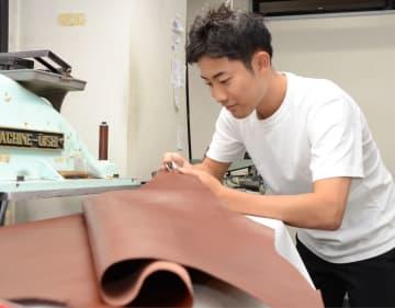 革靴の材料をチェックする上田誠一郎さん=2018年9月10日、大阪市浪速区