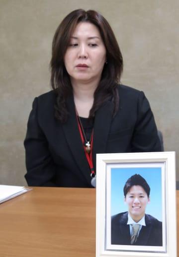 山本慎也さんの遺影を前に記者会見する母美保さん=14日、東京都千代田区