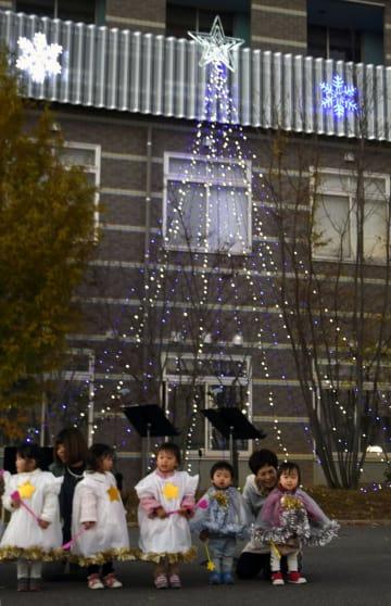 西日本豪雨で浸水した「まび記念病院」のイルミネーションの点灯式に参加した保育園児ら=14日夕、岡山県倉敷市真備町地区