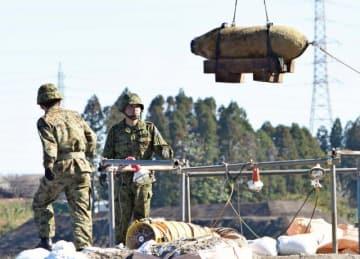 信管が外され、防護壁の中からクレーンで運ばれる不発弾(上)=14日午前、都城市南横市町