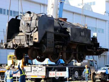 大型クレーンでつり上げられ、線路に移されるC11形蒸気機関車=14日午前、埼玉県久喜市北広島の東武鉄道南栗橋車両管区