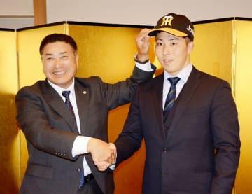 仮契約を結び、阪神の帽子をかぶってスカウトと握手を交わす片山雄哉捕手(右)=11月14日、福井県福井市内のホテル