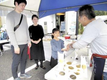 「きき米体験」後、いちほまれをプレゼントされる親子=11月3日、東京都世田谷区の駒沢公園ハウジングギャラリー