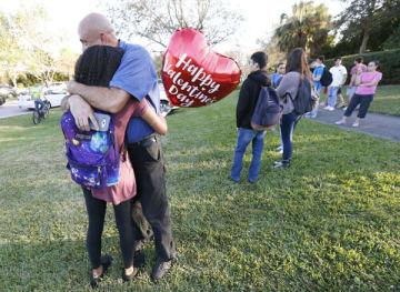 2月14日にフロリダの高校で起きた銃乱射事件で家族と抱き合う女子生徒(C)AP