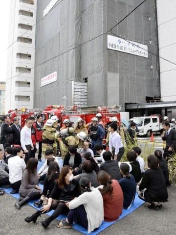ガス漏れで避難した職員ら=14日正午ごろ、徳島市幸町3の自治会館