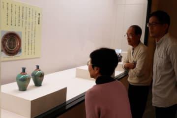 【瑞牙の県指定有形文化財「色絵窓山水文御神酒器」に見入る来場者=朝日町柿の町歴史博物館で】