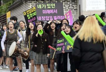 15日、ソウルの試験会場前で、受験生を応援する後輩たち(共同)