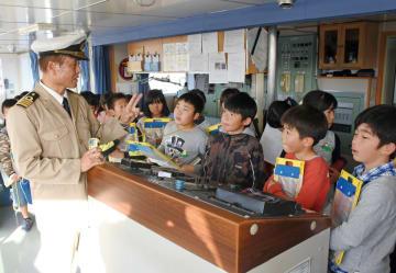 唐津東港に停泊中の「エメラルドからつ」に乗船し、向井善嗣船長からフェリーの運航を学ぶ西唐津小の3年生=同フェリーのブリッジ