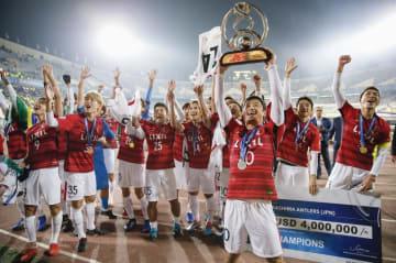 ACLで初優勝し、トロフィーを掲げてサポーターの声援に応える小笠原(手前)ら鹿島イレブン=テヘラン(共同)