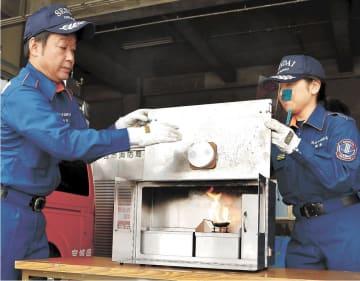 煙や熱を感知し、ランプが点灯した住宅用火災警報器の実験装置=仙台市青葉区の市消防局