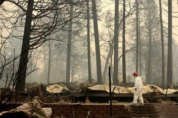 14日、米カリフォルニア州パラダイスで、山火事の焼け跡を捜索する救助隊員(ゲッティ=共同)