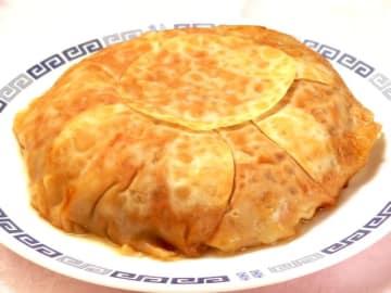 炊飯器で大きな餃子を作ります。内釜に餃子の皮を敷きつめ、あん(ひき肉種)をのせて皮をかぶせ、スイッチオンで完成します。