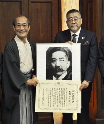 第2代京都市長を務めた西郷菊次郎への特別感謝状を受け取った孫の隆文さん(右)。左は門川大作京都市長=15日午前、京都市役所