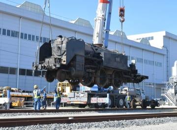 搬入された2両目のSLをクレーンで線路に移す社員ら=14日10時20分、埼玉県久喜市の東武鉄道南栗橋車両管区