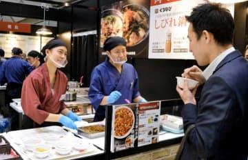 来場者(手前)に試食を勧め調理方法を紹介する日本食研ホールディングスの社員=14日午後、東京・有明
