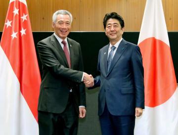 会談の冒頭、シンガポールのリー・シェンロン首相(左)と握手する安倍首相=15日、シンガポール(代表撮影・共同)