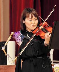 全身を使い、義手でバイオリンを弾く伊藤真波さん=三木市立豊地小学校