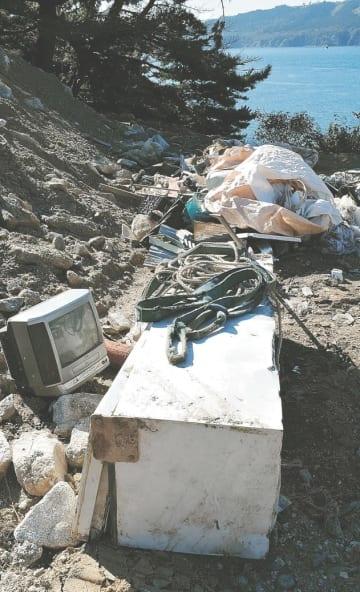 神社敷地内に放置された古い冷蔵庫やテレビ。近くには土砂(写真左)も積まれていた=4日、石巻市の金華山