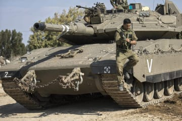 戦車から降りるイスラエル軍の兵士=13日、イスラエルとパレスチナ自治区ガザの境界付近(AP=共同)
