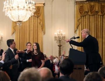 米ホワイトハウスでのトランプ大統領の記者会見で、質問するCNNテレビ記者(左端)のマイクに手を伸ばすスタッフ=7日(ロイター=共同)