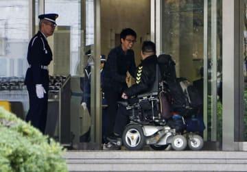 大阪地裁、大阪高裁の庁舎に入る車いすの男性。このあとボディーチェックと所持品検査を受ける=15日、大阪市