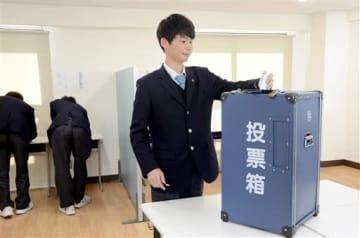 熊本市長選の模擬投票で、一票を投じる生徒=熊本市中央区