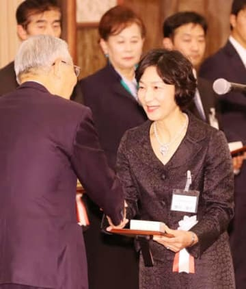 白石会長(手前左)から盾とメダルを受け取る関川副所長