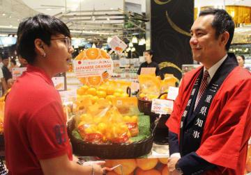 タイの消費者に南紀みかんを売り込む三重県の鈴木知事(右)=15日、バンコク(NNA撮影)