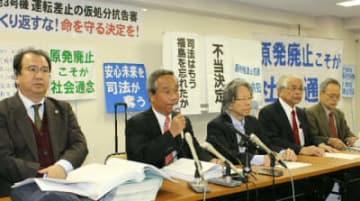 高松高裁決定を受けて会見する住民側の薦田伸夫弁護団長(左から2人目)ら=15日、高松市寿町
