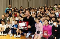 児童との記念撮影に応じるJ1神戸のポドルスキ選手(中央)=魚崎小学校