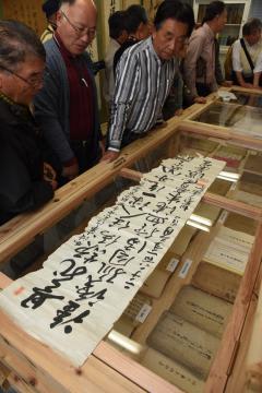 中村宝水が保管していた資料を示す、中村勝美さん(左から3人目)。手前に置かれているのは、富松正安が獄中で作った漢詩を書いた玉水嘉一直筆の書=筑西市関舘の中村宝水資料館