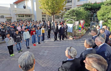 長崎市立城山小の児童(左側)から歓迎の言葉を受ける賢人会議の参加者=同校