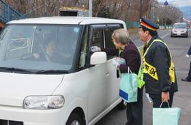 踏切手前で啓発資材をドライバーに手渡す町内会連合会役員ら
