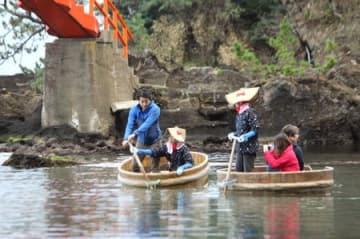 タイのテレビ番組の収録で、たらい舟に乗る俳優の佐野ひろさん(左)=13日、佐渡市小木の矢島・経島