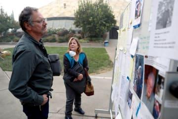 15日、米カリフォルニア州の山火事に関連し、安否不明者のリストで知人を捜す人々(ロイター=共同)