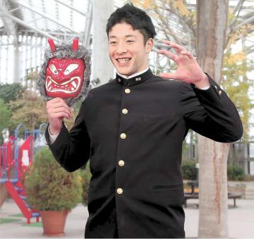 ナマハゲのお面を手に笑顔を見せる吉田
